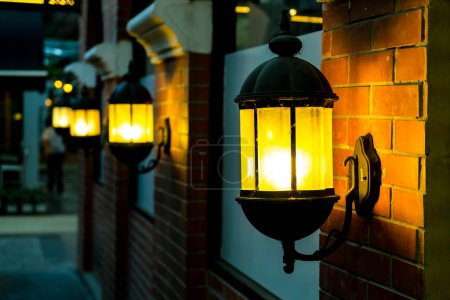 lamp against a red brick wall at night.