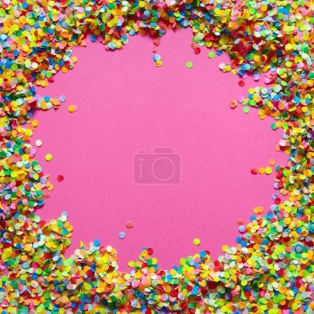 Marco hecho de confeti de color. Fondo rosa .