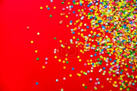 Marco hecho de confeti de color. Fondo rojo .