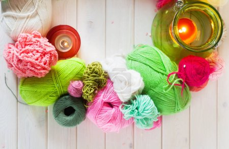 Yarn, candles, knitting on a white background wood. Pink and gre
