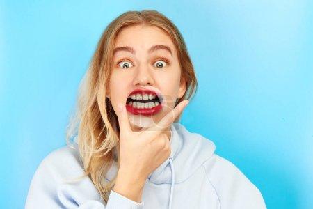 Photo pour Jeune femme magnifique avec loupe montre le sourire blanc neige, des dents saines. Concept dentaire drôle, clinique de stomatologie patient isolé sur fond bleu - image libre de droit