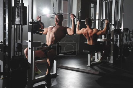 Photo for Portrait of fitness athlete man with muscular body does exercises on sports equipment in the gym, workout arm muscles, pumping biceps and triceps - Royalty Free Image