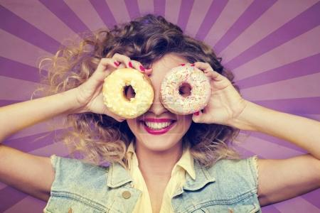 Curly girl hiding face with donuts on stripped purple background