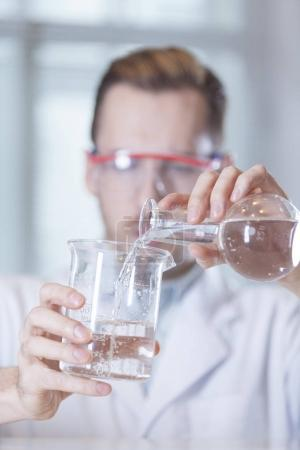 beaker and flask with liquids in hands