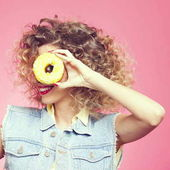 young woman  looking through donut