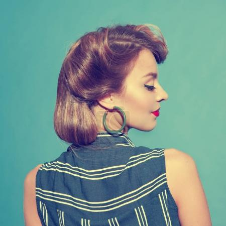Back view of young woman with classical pin - up hairstyle