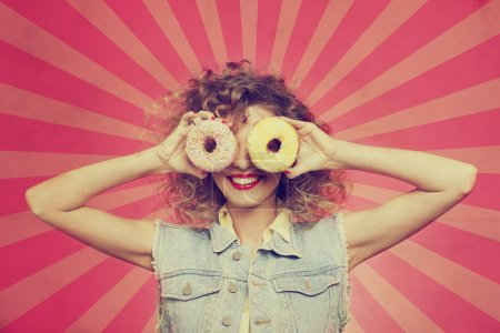 young woman put face to donut