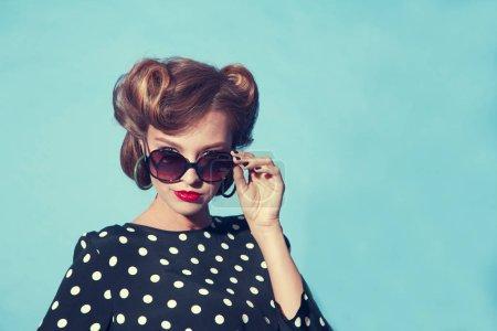 Photo pour Portrait d'une jeune femme avec des lunettes de soleil de style rétro sur fond bleu - image libre de droit
