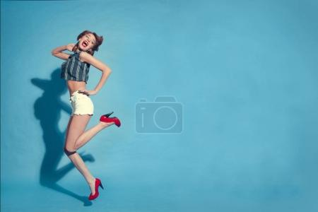Full body view of pin - up styled woman on blue background