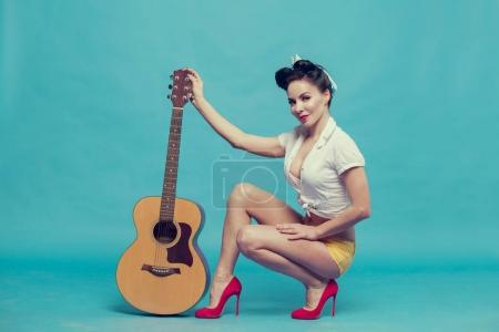 young woman guitarist on blue background
