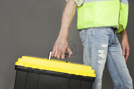 Builder wearing green waistcoat and jeans carrying tool box in hand