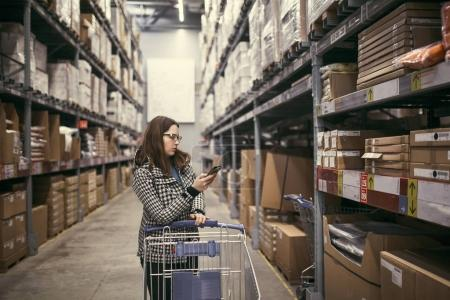 girl with phone looking for goods on the shelf