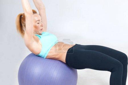 âge de la femme athlétique travailler avec fitball sur le fond gris