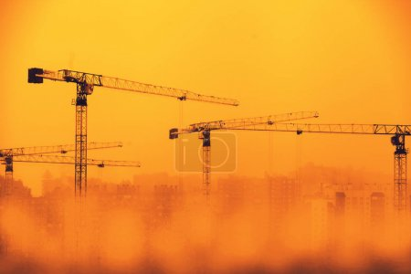 Photo pour Grues de construction dans le brouillard contre un ciel orange - image libre de droit