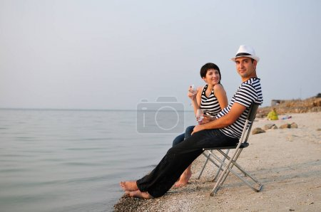 couple sitting on beach with wine