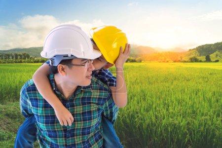 El padre constructor está llevando a su hijo en Paddy campo de naturaleza para agr.