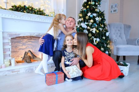 Father and daughters posing for family photo in photo studio.
