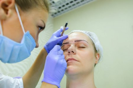 Girl Specialist mikropigmentirovaniyu corrects shape of eyebrows