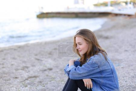 Portrait of cute girl who smiles and looks at camera, sitting on