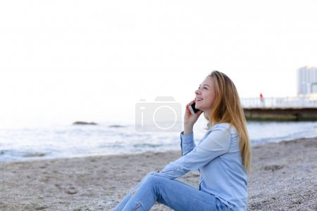 Beautiful female speaks on mobile with smile and sits on beach n