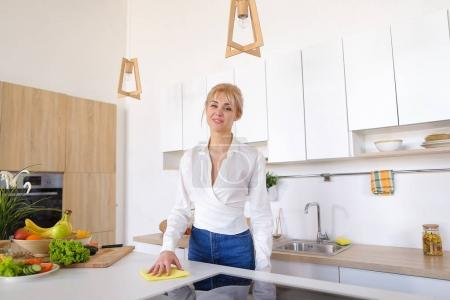 Beautiful housewife diligently follows order and wipes surface,