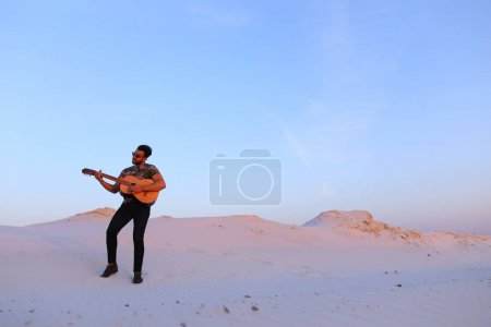 Arab guy goes inspired by beauty of desert and plays guitar stri