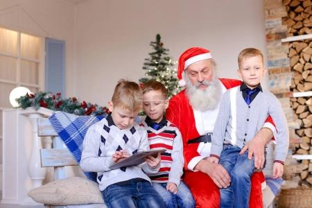 Little boys  with Santa Claus playing with tablet.