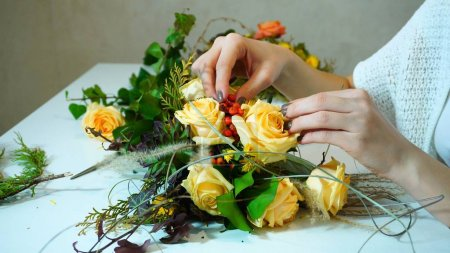 Close-up shot of  hands of florist girl who completes  creation
