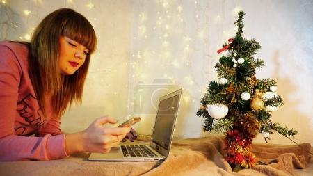 Cheerful female person talking on phone and typing message on la