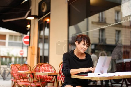 aged female screenwriter working with scenario in laptop.