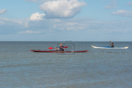 Women paddling two colorful kayaks in the blue sea