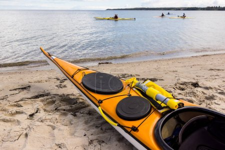 A yellow sea kayak on the shore and four kayaks along the beach