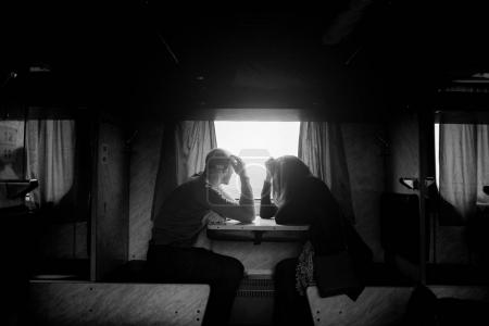 A man and a woman are sitting near a window in a train. B w photo