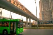 """Постер, картина, фотообои """"зеленые троллейбус едет по дороге в город. на фоне высотных зданий и на верхней пешехода"""""""