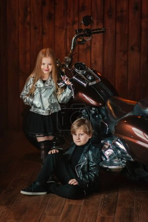 girl holding hand on motorcycle with boy
