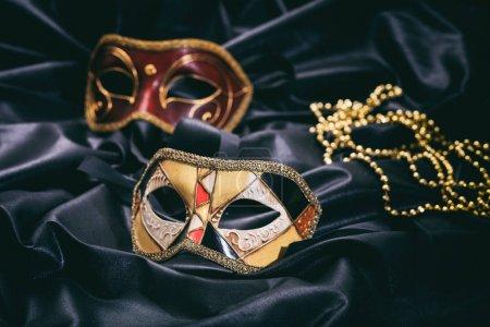 Photo pour Masques de carnaval isolés sur fond satiné noir - image libre de droit