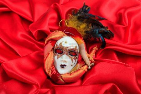 Photo pour Masque de carnaval isolé sur fond de satin rouge - image libre de droit