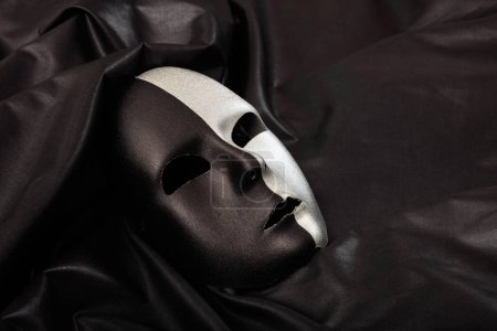 Photo pour Masque de carnaval noir et argent isolé sur fond satiné noir - image libre de droit