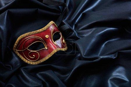 Photo pour Masque de carnaval rouge isolé sur fond satiné noir - image libre de droit