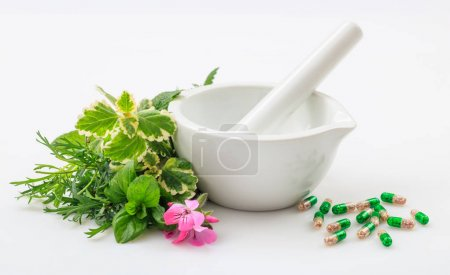 Mortar, herbs and pills on white background