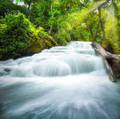 Waterfall pool landscape, beautiful waterfall with sunlight rays in deep forest at Erawan National Park, Thailand