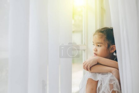 Photo for Depressed Little girl near window at home, closeup - Royalty Free Image