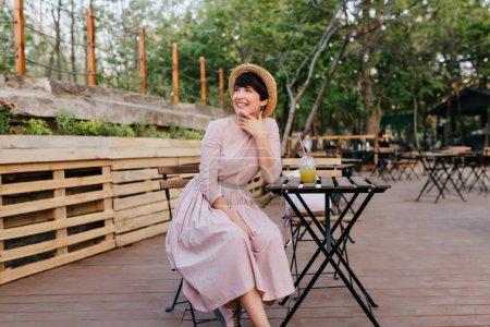 Photo pour Fille brune excitée en belle robe à l'ancienne touchant le visage avec un charmant sourire se reposant dans un café en plein air. Portrait d'une jeune femme joyeuse dans des boissons vestimentaires d'époque jus dans un restaurant en plein air. - image libre de droit