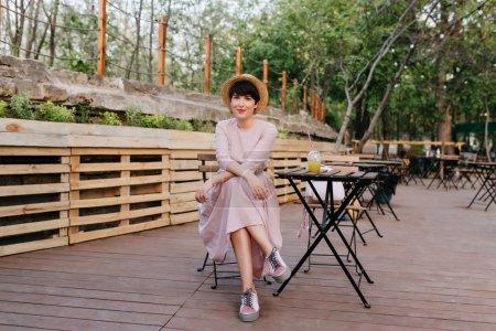 Photo pour Une élégante petite fille aux cheveux courts se repose dans le restaurant du parc et profite du week-end en été. Belle jeune dame vétuste, vêtue d'une tenue désuète, rafraîchissante dans un café en plein air et un cocktail de boissons.. - image libre de droit