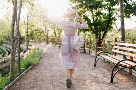 Photo pour Fille mince en longue robe de coton et chapeau de paille tendance se promenant le long de la belle ruelle aux arbres verdoyants. Portrait extérieur du dos d'une jeune femme en costume romantique vintage portant un sac à dos blanc. - image libre de droit