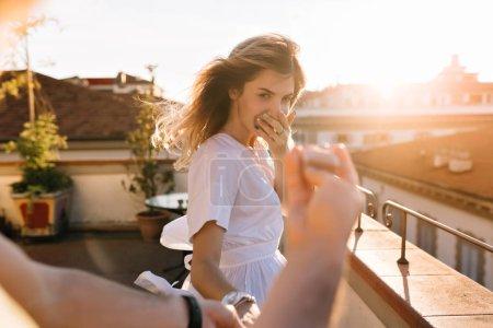 Photo pour Portrait extérieur d'une jeune femme joyeuse, en chemise blanche, la main d'un homme tenant un anneau au premier plan. Une jolie blonde adorée à la caméra s'est fait offrir de se marier. - image libre de droit