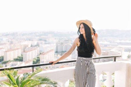 """Photo pour Fille brune de rêve au chapeau d """"été branché qui se rafraîchit sur le toit et qui jouit d'une vue panoramique sur la ville. Élégante dame aux cheveux longs noirs posant avec le sourire sur le pont d'observation pendant le repos à l'hôtel. - image libre de droit"""