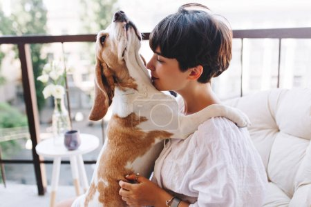 Photo for Romantic brunette girl with trendy haircut kissing beagle dog in the neck while posing on balcony. Portrait of graceful lady in white bathrobe sitting in chair with puppy and gently hugging him. - Royalty Free Image