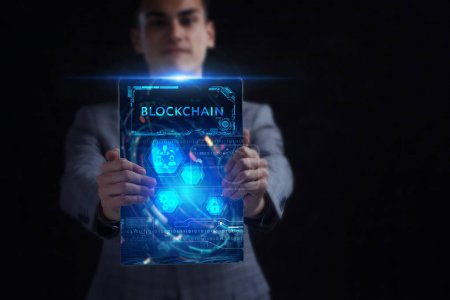 Photo for Business, Technology, Internet and network concept. Young businessman working on a virtual screen of the future and sees the inscription: Blockchain - Royalty Free Image