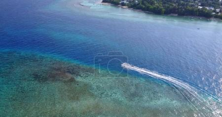 v03454 Aerial flying drone view of Maldives white sandy beach on sunny tropical paradise island with aqua blue sky sea water ocean 4k boat sailing